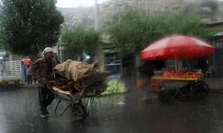 An Afghan labourer uses a wheelbarrow to