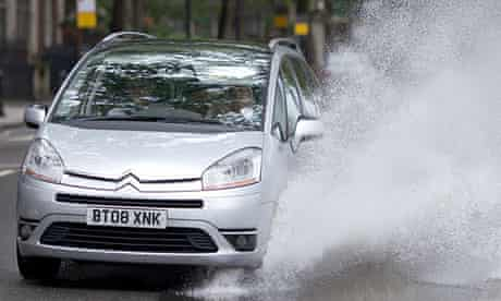 A car drives through a large puddle after heavy rain
