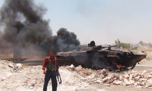 A Syrian rebel standing near a burning army tank