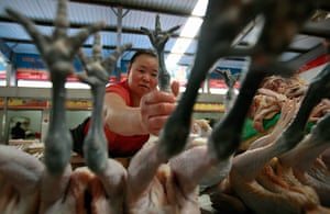 24 hours: Huaibei, China: A vendor holds a chicken foot for sale at a market