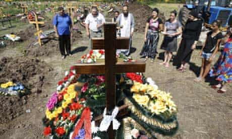 Relatives and friends mourn over the grave of a flash flood victim at the Krymsk central cemetery