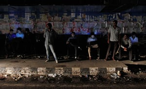 India blackout ends: Commuters work on their laptops as they wait for the bus