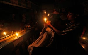India blackout ends: A customer holds a candle as he gets his haircut at a barber's shop