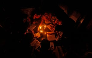 India blackout ends: A teacher conducts a lesson in the light of kerosene lamps