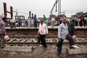 India blackout ends: Stranded passengers wait for train services to resume at a railway station