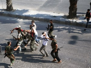 Rebel Free Syrian Army fighters drag along a street captured policemen who the FSA allege are  shabiha  or pro-regime militiamen in Aleppo