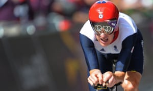 Bradley Wiggins crosses the finish line to win gold. The Olympic rings on the road on the finish line are reflected in his visor. Photograph: Tom Jenkins for the Guardian