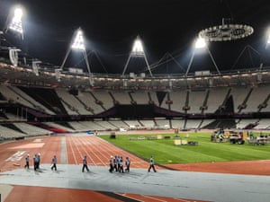 Workers prepare the Olympic stadium for the closing ceremony after the finish of the atheltics