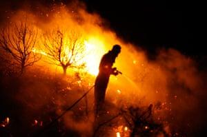 24 hours : A volunteer firefighter battles flames in a forest fire near Guadalajara
