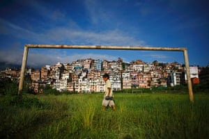 24 hours : A boy walks past a football post in front of the ancient city of Kirtipur