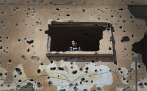 24 hours : A Palestinian man looks out from a destroyed house
