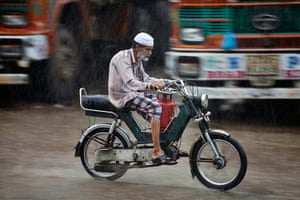 24 hours : A man carries a gas cylinder on his motorbike in heavy rain in Hyderabad