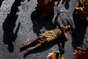 24 hours : A devout Hindu holds a coconut as an offering as he rolls along the ground