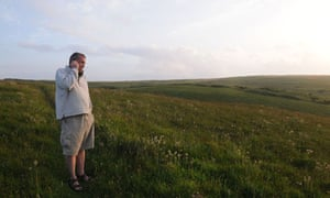 Man talking on mobile phone in countryside
