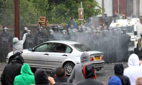 A youth throws a chair over a burning car towards police in the Ardoyne area of Belfast on 12 July