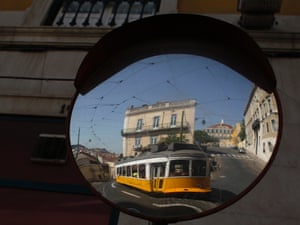 A view of a tram passing through is reflected in a road safety mirror in downtown Lisbon.