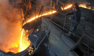 A worker monitors molten iron pouring into a furnace at steel manufacturing plant in Hefei, Anhui province, China. China's daily crude steel output fell 0.8 percent to 1.99 million tonnes in July from the previous month.