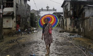 A Filipino muslim woman walks through a neighbourhood damaged by recent flooding in Manila, Philippines. The country has been hit by  tropical storm Kai-Tak.