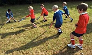 Schoolchildren playing hockey on school playing fields.