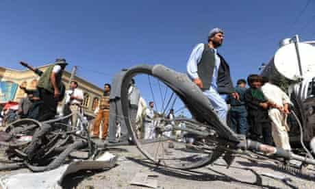 Afghan locals inspect the site of a bicycle bomb explosion in Herat