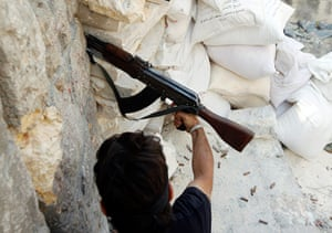 Syrian Conflict: Syrian Conflict: A Free Syrian Army fighter fires an AK-47 rifle in Aleppo
