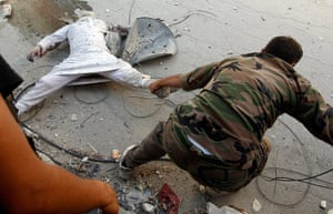 Syrian Conflict: A Free Syrian Army fighter drags a dead man