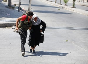 Syrian Conflict: A Free Syrian Army fighter helps a woman