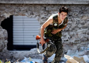 Syrian Conflict: A Free Syrian Army fighter runs for cover