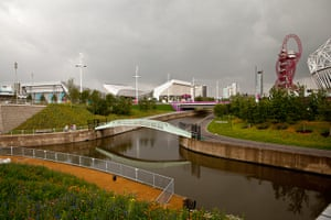 London Legacy: Photograph showing an iron bridge over canal with Olympic Orbit behind