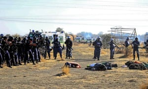 South African police check the bodies of striking  workers shot dead near Marikana platinum mine