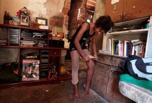 From the agencies: Marie Ellen da Silva adjusts her stockings in her home
