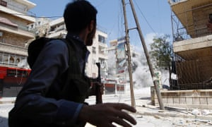 A Free Syrian Army fighter runs for cover as a Syrian Army tank shell hits a building across a street during clashes in the Salaheddine neighbourhood of central Aleppo.