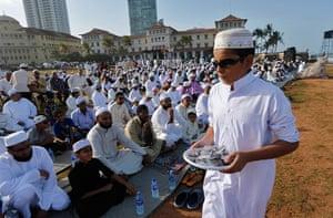 Eid al-Fitr begins: A Sri Lankan Muslim boy distributes sweets in Colombo, Sri Lanka