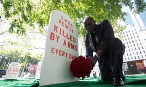 A campaigner lays flowers in a mock graveyard next to the UN building in New York