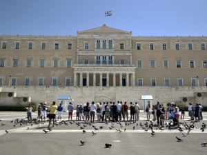 Tourists watch the presidential  guards at the monument of the Unknown Soldier in front of the Greek Parliament in Athens on August 20, 2012.