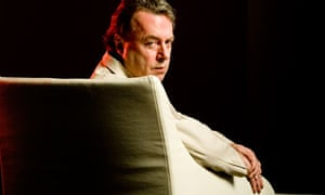 Christopher Hitchens looking over back of armchair