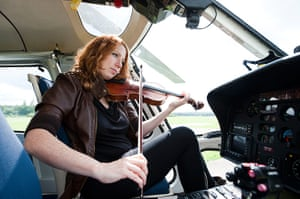 Mittwoch Aus Licht: A woman sits inside a helicopter playing a violin