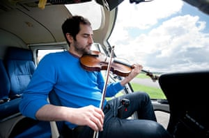 Mittwoch aus Licht: A man sits in a helicopter playing the viola