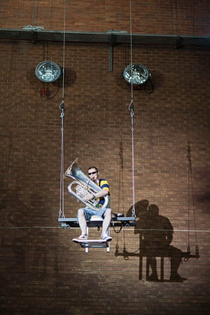 Mittwoch aus Licht: A man plays the tuba on a trapeze