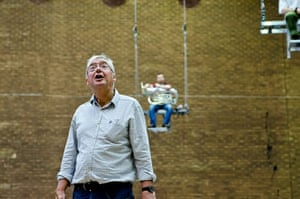 Mittwoch aus Licht: A man looks up with a tuba player on a trapeze behind him
