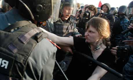 A woman is restrained by riot police in Moscow
