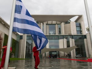 Workers raise the Greek flag in the yard of the Chancellery in Berlin, August 24, 2012.