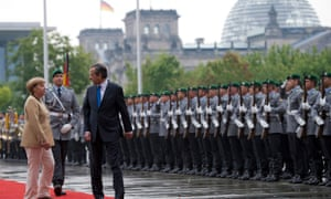 German Chancellor Angela Merkel, left, and Prime Minister of Greece Antonis Samaras, right, review the honor guard prior to their meeting at the chancellery in Berlin, Germany, Friday, Aug. 24, 2012