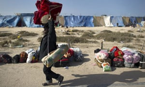 A sub-Saharan migrant from carries his belongings at a makeshift camp in Libya