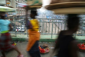 Adolphus: Vegetable sellers walk past a pedestrain bridge in Cotonou, Benin Republic