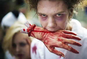 Zombie walk: A zombie holds a fake bloody hand in his mouth