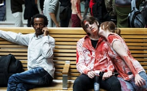 Zombie walk: A bemused resident shares a bench with a zombie couple