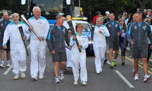 The Paralympic flame being carried through Harrow on its journey to the Olympic stadium