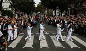 The Paralympic flame is carried across Abbey Road in north-west London on 29 August 2012.