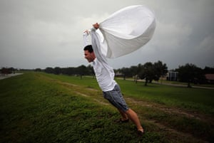 Tropical storm Isaac: Man holds a sheet open in the wind on the levee near Lake Pontchatrain